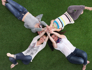 Four young women lying on green grass