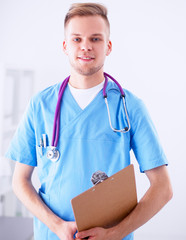 Doctor with stethoscope standing , crossed arms, on white
