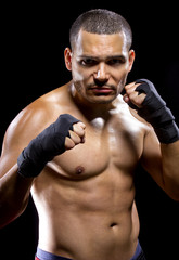 fit latino MMA fighter flexing muscles on black background