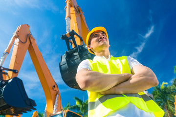 Asian builder in front of shovel excavator