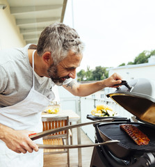 Mann grillt auf seinem Balkon