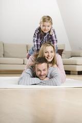 Eltern und Tochter (3-4) entspannen auf Teppich, Portrait