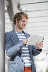 Der lächelnde Mann mit Tablet-PC
