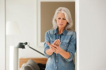 Ältere Frau mit Schmerzen an der Hand im Wohnzimmer