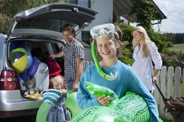 Deutschland, München, Familie stellt Gepäck im Kofferraum
