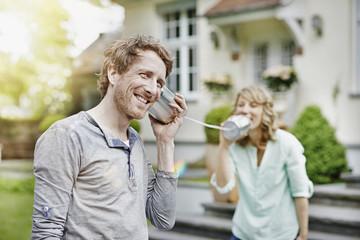 Deutschland, Hessen, Frankfurt am Main, Paar im Garten spielen mit Blechdose Telefon
