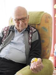 Alter Mann im Sessel drückt Stress-Ball