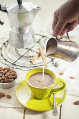 Mandelmilch in Tasse Kaffee giessen