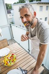 Porträt, Mann mit Salat auf seinem Balkon