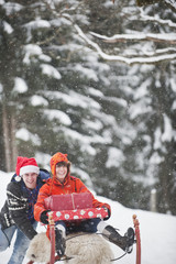 Österreich, Salzburg Land, Flachau, Junge Frau sitzt auf Schlitten mit Weihnachtspäckchen und Mann schiebt sie