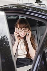 Deutschland, Geschäftsfrau sitzt in einem Auto mit zwei Smartphones