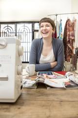 Portrait, lachende Mode-Designerin in ihrem Atelier