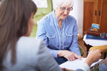 Frau erklärt einer anderen Frau ein Dokument