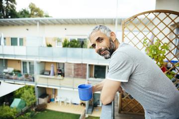 Mann entspannt mit Tasse Kaffee auf dem Balkon
