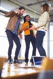 Drei glückliche kreative Menschen tanzen auf einem Konferenztisch