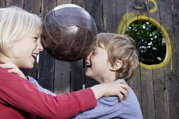 Deutschland, Nordrhein-Westfalen, Köln, Jungen spielen mit Ball auf Spielplatz, Lächeln