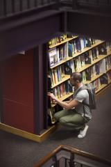 Student in einer Bibliothek, an Bücherregal