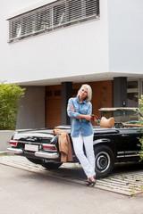Ältere Frau lehnt an einem Cabrio vor Einfamilienhaus