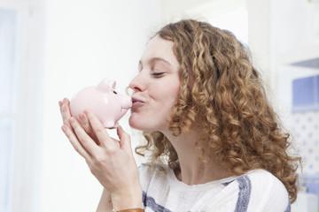 Deutschland, Bayern, München, junge Frau küsst Sparschwein lächelnd