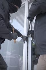 Zwei Einbrecher öffnen Terrassentür eines Einfamilienhauses mit Hammer und Brecheisen tagsüber, Teilansicht