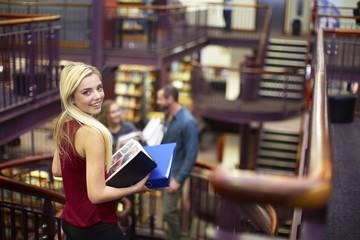 Porträt der lächelnden Studentin in einer Bibliothek