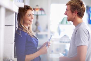 Lächelndes junges Paar in einem Glas-Verkaufsraum