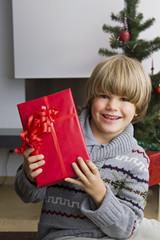 Portrait des glücklichen kleinen Jungen mit Weihnachtsgeschenk