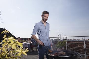 Deutschland, Berlin, Mann beim Grillen, lächelnd