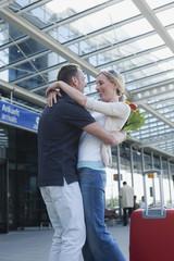 Deutschland, Leipzig-Halle, Flughafen, Paar umarmt sich, Mann, hält Blumen