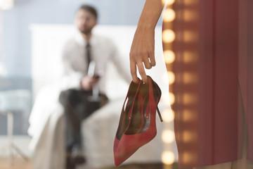 Frau mit hohen Absätzen mit Mann im Schlafzimmer