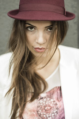 Porträt der jungen Frau mit langen braunen Haaren trägt Hut