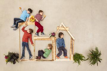 Kinder spielen im Freien, bauen eine Holzhütte