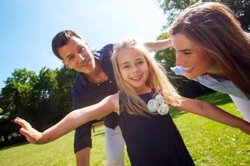 Kleines Mädchen spielt im Park mit ihren Eltern