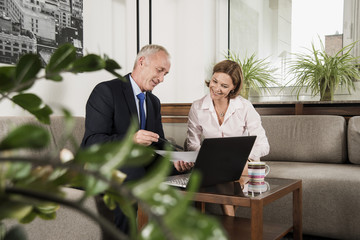 Geschäftsmann mit Laptop im Gespräch mit Frau