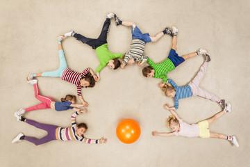 Kinder fliegen um einen Ball herum
