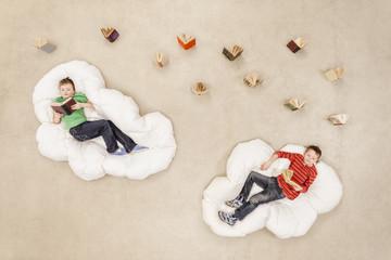 Jungen liegen auf Wolken und lesen