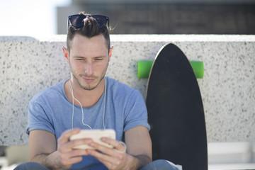 Skateboarder,Pause mit Smartphone