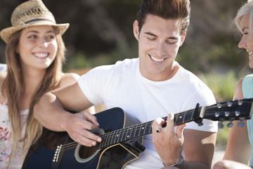 Glückliche Freunde mit Gitarre im Freien