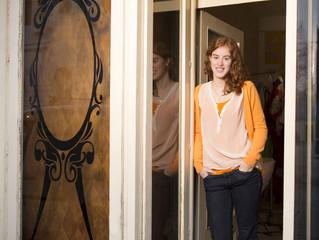 Mode-Designerin steht am Eingang ihres Ateliers