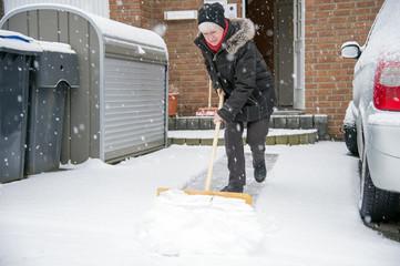 Deutschland, Grevenbroich, Frau, Schneeschaufeln vor dem Haus