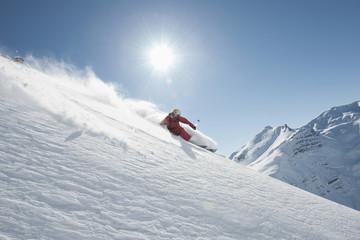Österreich, Arlberg. Mann beim Skifahren bergab