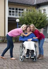 Teenager-Mädchen und junge Frau mit ihrem Freund im Rollstuhl