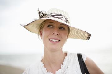 Lachende Frau mit Strohhut im Freien