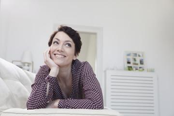 Deutschland, Bayern, München, Frau entspannt auf der Couch, lächelnd