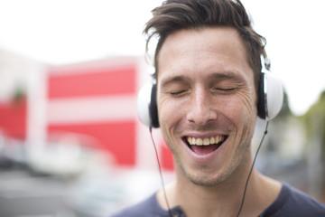 Porträt singender junger Mann hört Musik mit Kopfhörern