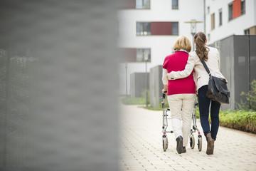Enkelin hilft ihrer Großmutter zu Fuß mit Rollator