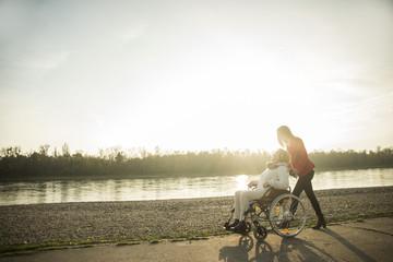 Erwachsene Enkelin hilft ihrer Großmutter im Rollstuhl