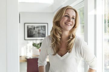 Portrait der glücklichen Frau in ihrem hellen, modernen Haus