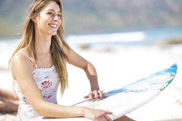 Junge Frau sitzt am Strand mit Surfbrett
