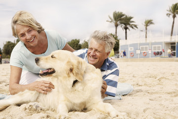 Spanien, Älteres Paare mit Hund am Strand in Palma de Mallorca, lächelnd